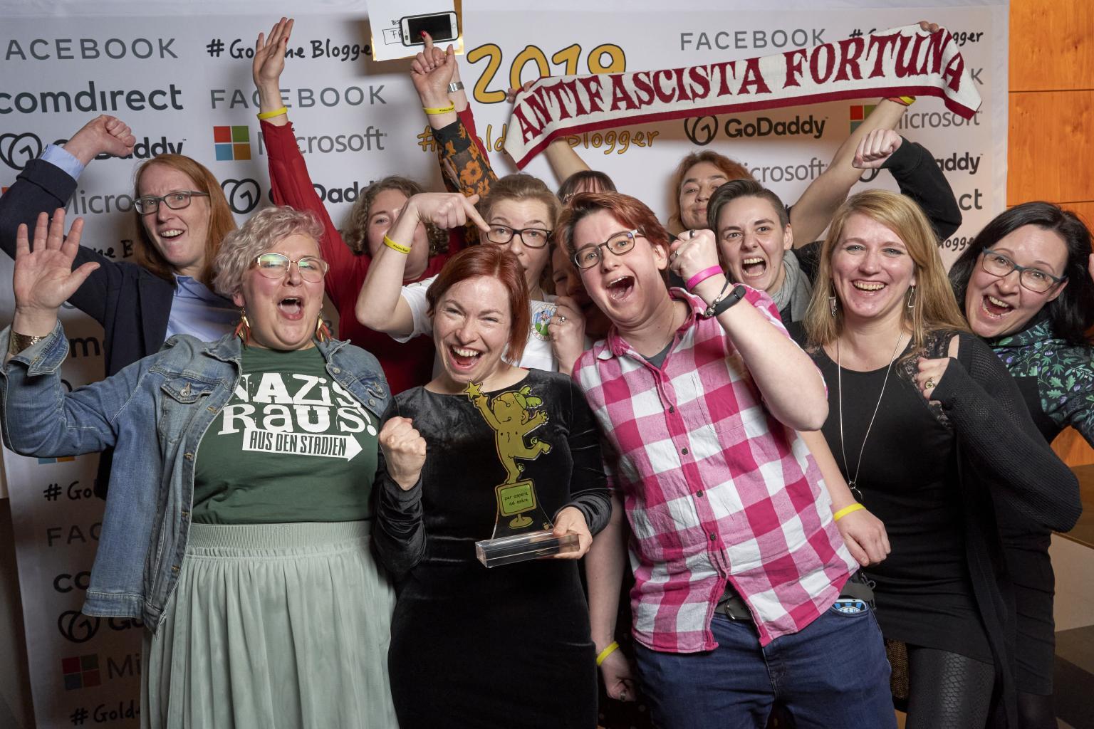 Die FRÜF-Crew mit ihrem Pokal der Goldenen Blogger bei der Preisverleihung. Alle jubeln begeistert, reißen die Hände in die Luft und freuen sich.